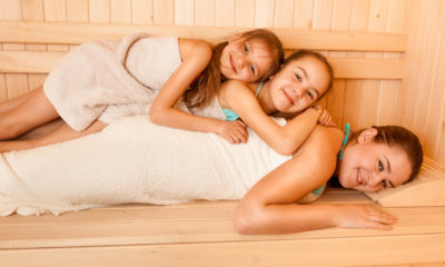 Portrait of little girls lying on mothers back at sauna